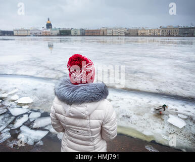 Woman in red hat near frozen Neva River with duck and Isaac's Cathedral on other side in winter Saint-Petersburg, - Stock Photo