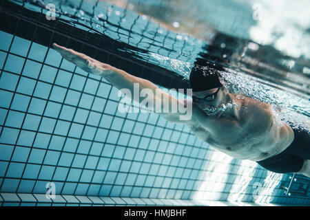 Young man swimming the front crawl in a pool. Underwater shot of pro swimmer practising for race in swimming pool. - Stock Photo