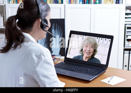 Female doctor in her surgery office with headset in front of her laptop, an x-ray of a foot in hand, talking to - Stock Photo
