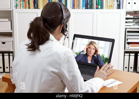 Female doctor or pharmacist in her surgery office with headset in front of her computer talking via video chat with - Stock Photo