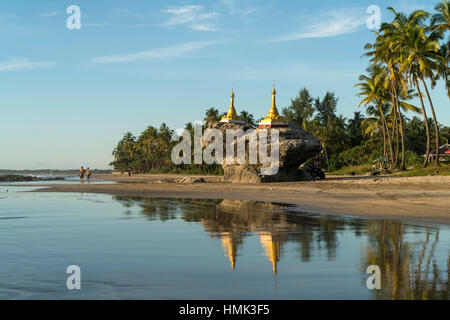Golden pagodas on rocks at palm beach, Ngwe Saung, Myanmar - Stock Photo