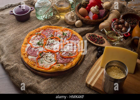 Delicious italian pizza served on sackcloth - Stock Photo