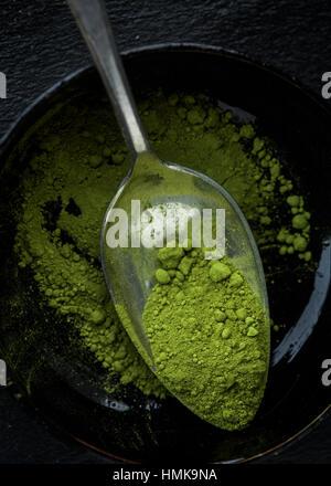 A bowl of matcha tea powder on a spoon - Stock Photo