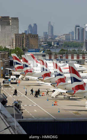 tail-fins of British Airways BA CityFlyer Embraer 170s parked in a row at London City with skyscrapers behind - Stock Photo