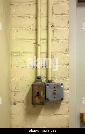 Old light switches on a brick wall. - Stock Photo
