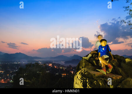Laotian children at Phou Si Hill and sunset overview of the Mekong River and hills around Luang Prabang, Laos, South - Stock Photo