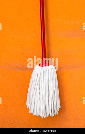 Mop hanging from colourful wall of brightly coloured house in Burano - bright colors of Burano, Venice, Italy in - Stock Photo