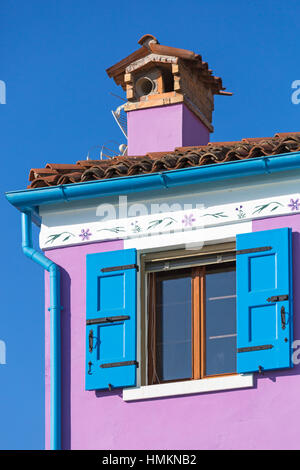 Blue wooden shutters of window on purple pink house and blue sky at Burano - Bright colors of Burano, Venice, Italy - Stock Photo
