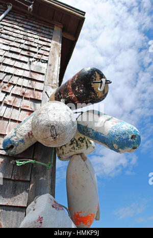 Old buoys hung an a Canadian house as decorative items. - Stock Photo