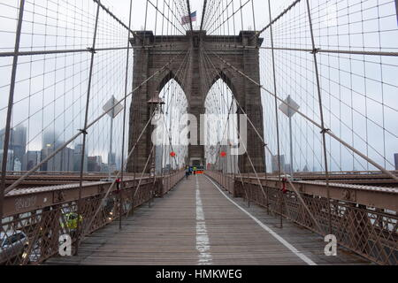 A Tower of Brooklyn Bridge in New York City in a Foggy Day - Stock Photo