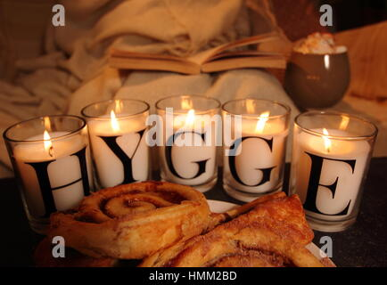 A man relaxes with a book, pastries and a warm drink in the glow of candles that depict 'hygge' the Danish concept - Stock Photo