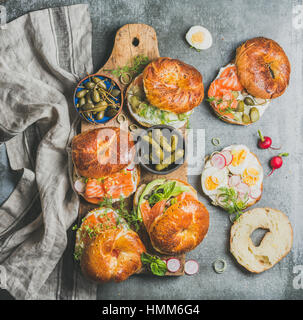 Variety of bagels with different fillings on rustic wooden board - Stock Photo