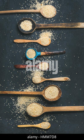 Quinoa seeds in different spoons over black stone background - Stock Photo