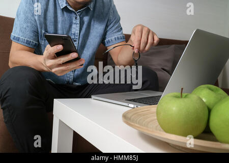 hipster hand using laptop compter and mobile payments online business,eyeglasses,sitting on sofa in living room,green - Stock Photo
