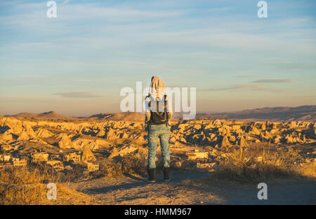 Young woman traveller standing at sunrise, Cappadocia, Central Turkey - Stock Photo