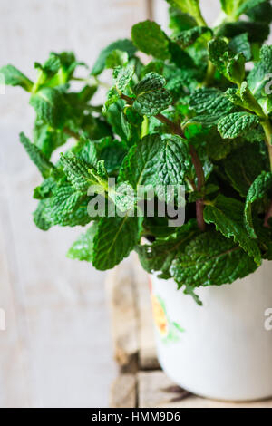 Bundle of fresh organic mint in an enamel mug on weathered wood box, spring or summer, natural light, outdoors - Stock Photo