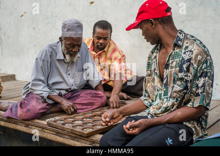 Men plays bao, mancala game, on a street of Stone Town, Zanzibar, Tanzania - Stock Photo