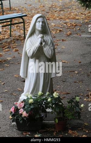 Sculpture de Bernadette Soubirous priant devant la statuette de la Vierge-Marie. Grotte de Lourdes. Couvent Saint - Stock Photo
