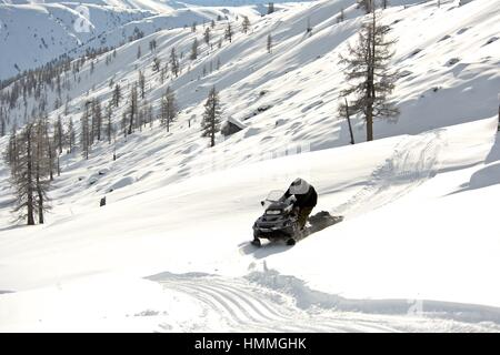 Man driving sports snowmobile in a sunny day - Stock Photo