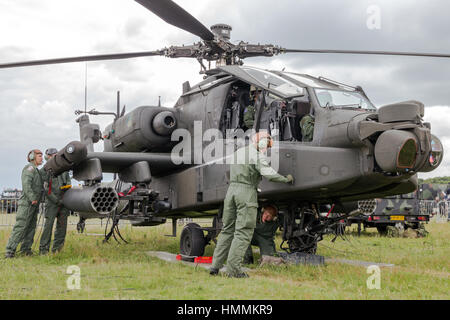 GILZE-RIJEN, NETHERLANDS - JUNE 20, 2014: Ground crew preparing a AH-64 Apache attack helicopter at the Royal Netherlands - Stock Photo