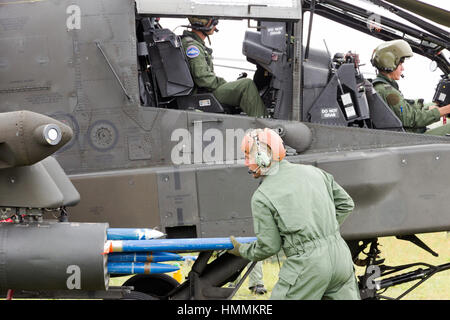 GILZE-RIJEN, NETHERLANDS - JUNE 20, 2014: AH-64 Apache attack heliocopter being armed with rockets at the Royal - Stock Photo