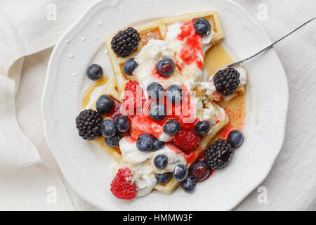 Waffles with raspberries, blueberries, whipped cream, berry fruit sauce and maple syrup - Stock Photo