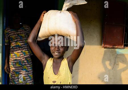 KENYA, County Siaya, village Kotanega, boy with maize flour bag infront of posho mill / KENIA, kleine Maismuehle, Junge mit Mehlsack