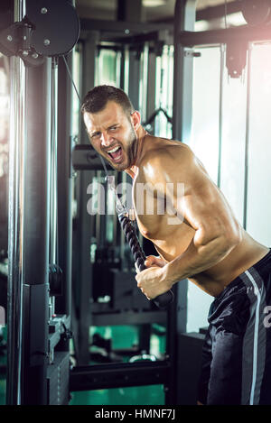 Young adult man doing triceps rope pushdown exercise in gym. - Stock Photo