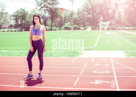 Young woman standing on athletics track during hot summer day. Toned image. - Stock Photo