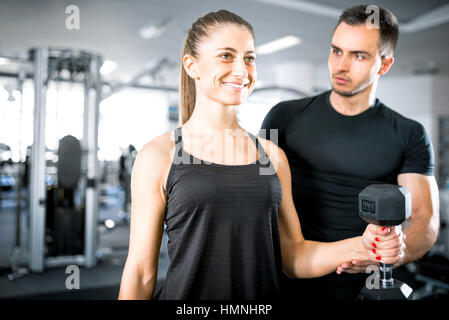 Young adult woman working out in gym, doing bicep curls with help of her personal trainer. - Stock Photo