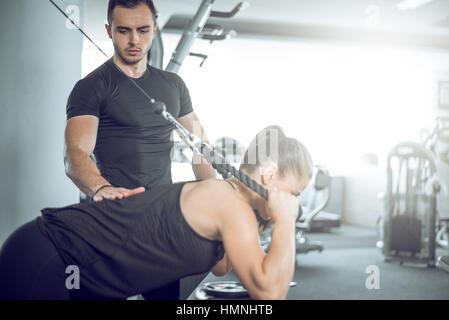 Young adult personal fitness trainer supporting his client while doing overhead rope extension. - Stock Photo