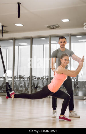 Young adult girl doing suspension rope exercise together with her personal private coach. - Stock Photo