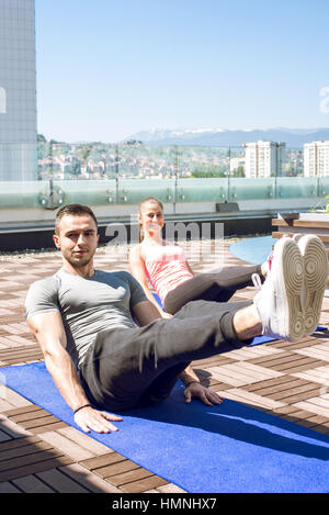 Young fitness couple doing legs up crunches outdoor on rooftop. - Stock Photo
