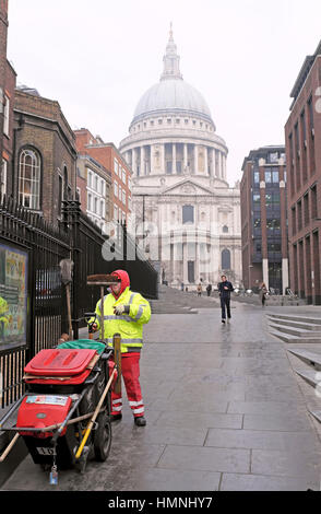 Street cleaner with dustcart in winter clothing working near St Pauls Cathedral in the City of London, UK   KATHY - Stock Photo