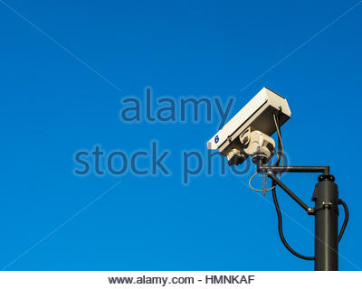 CCTV camera in silhouette on pole. Background is blue sky.  Concept of security, surveillance, being watched.  Copy - Stock Photo