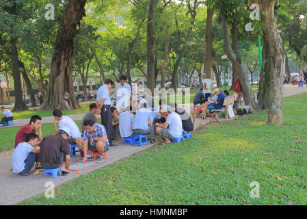 People play traditional board game in Lenin Statue Park in Hanoi Vietnam. - Stock Photo