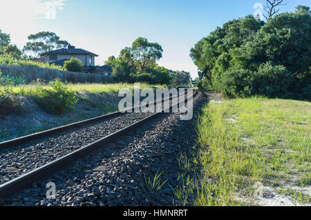 Rail tracks winding into the distance in rural area - Stock Photo