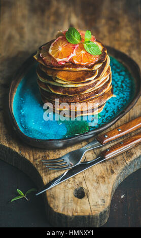 Homemade pancakes with honey, bloody orange slices and mint leaves - Stock Photo