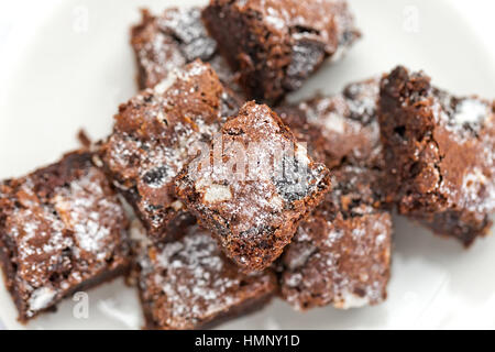 Delicious Freshly baked homemade cookies and cream brownie pieces on a white plate. Selective focus on the top of - Stock Photo