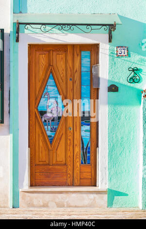 Ornate door with stained glass window inserts with flamingos on of house at Burano, Venice, Italy in January - Stock Photo