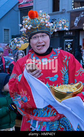 A man in costume making a funny face at the Chinese New Years Day Parade in Chinatown, downtown Flushing, New York - Stock Photo