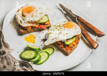 Breakfast toasts with fresh vegetables and fried egg on plate - Stock Photo