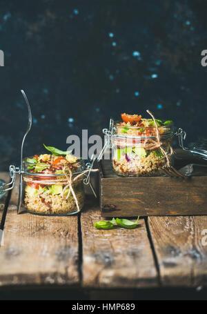 Homemade quinoa salad with tomatoes, avocado, basil in jars - Stock Photo