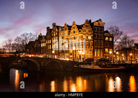 Amsterdam canal houses in traditional style next to a bridge over Prinsengracht en Brouwersgracht canals illuminated - Stock Photo