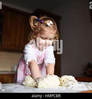 pretty little girl having fun kneads dough - Stock Photo