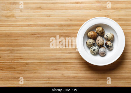 Plate with quail eggs on wooden table. Top view - Stock Photo