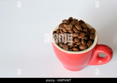 Coffee beans in a red espresso cup on a white background - Stock Photo