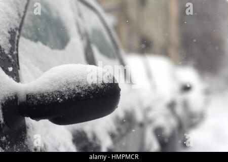 close up of black car side rear mirror with snow falling in winter time on a city street - Stock Photo