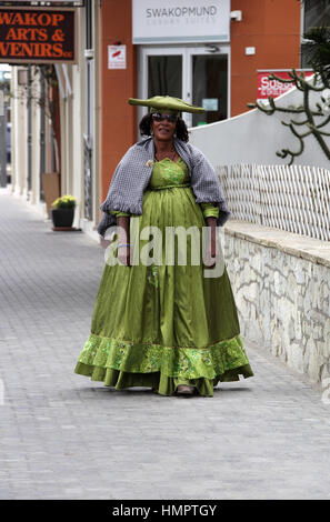 Herero woman wearing traditional dress at Swakopmund in Namibia - Stock Photo
