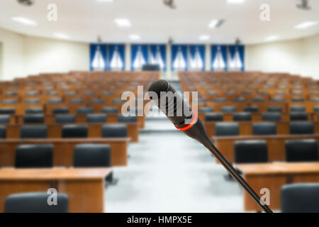 Microphone with blurred photo of empty conference hall or seminar room in background. Business meeting concept - Stock Photo
